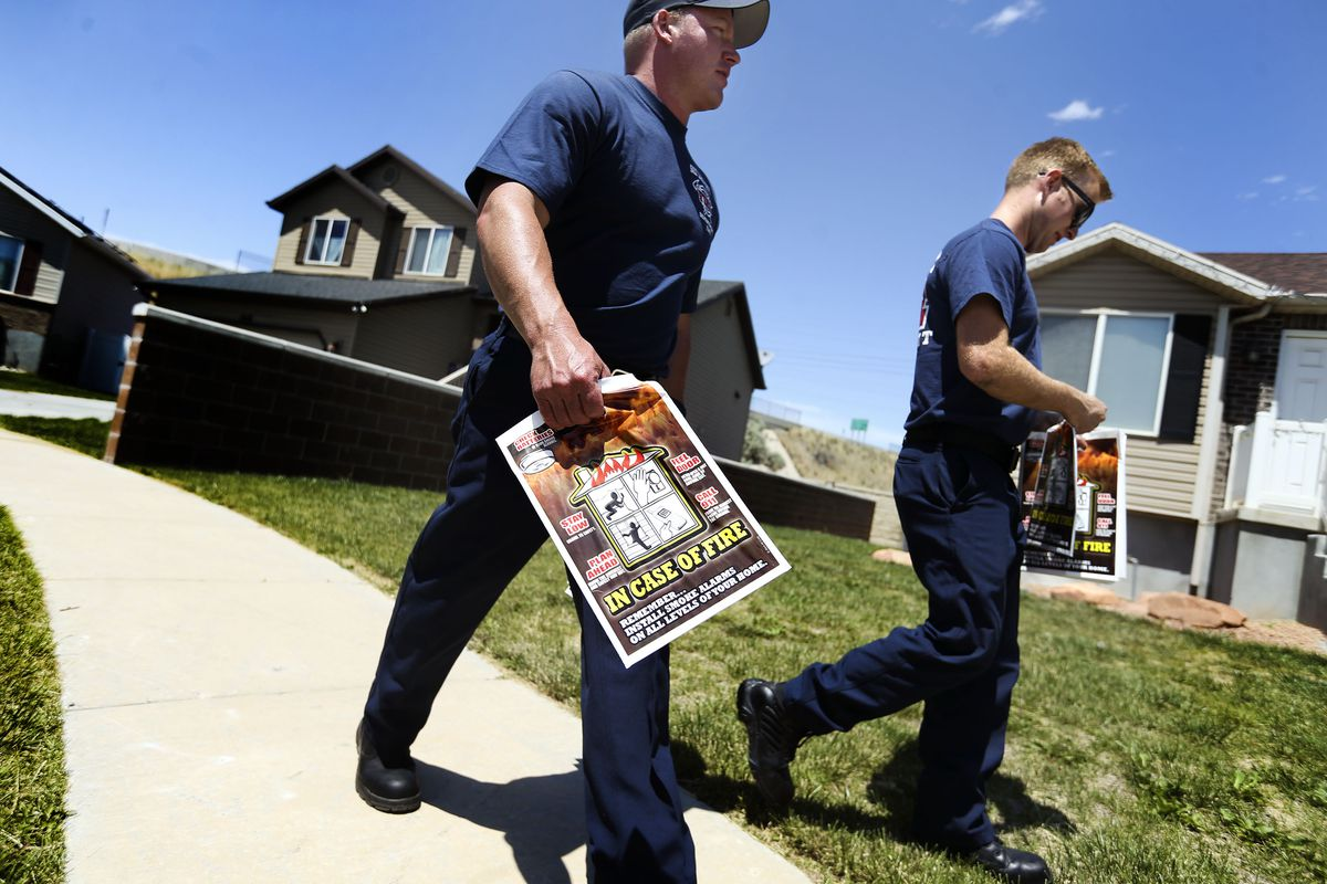 Firefighters Derek Mickelson, left, and Dylan Hansen deliver Ready, Set, Go! wildland fire action guides to resents on the west side of Salt Lake City on Saturday, June 5, 2021. The Ready, Set, Go! program seeks to share information with residents on how they can successfully become prepared in the event of a wildland fire.