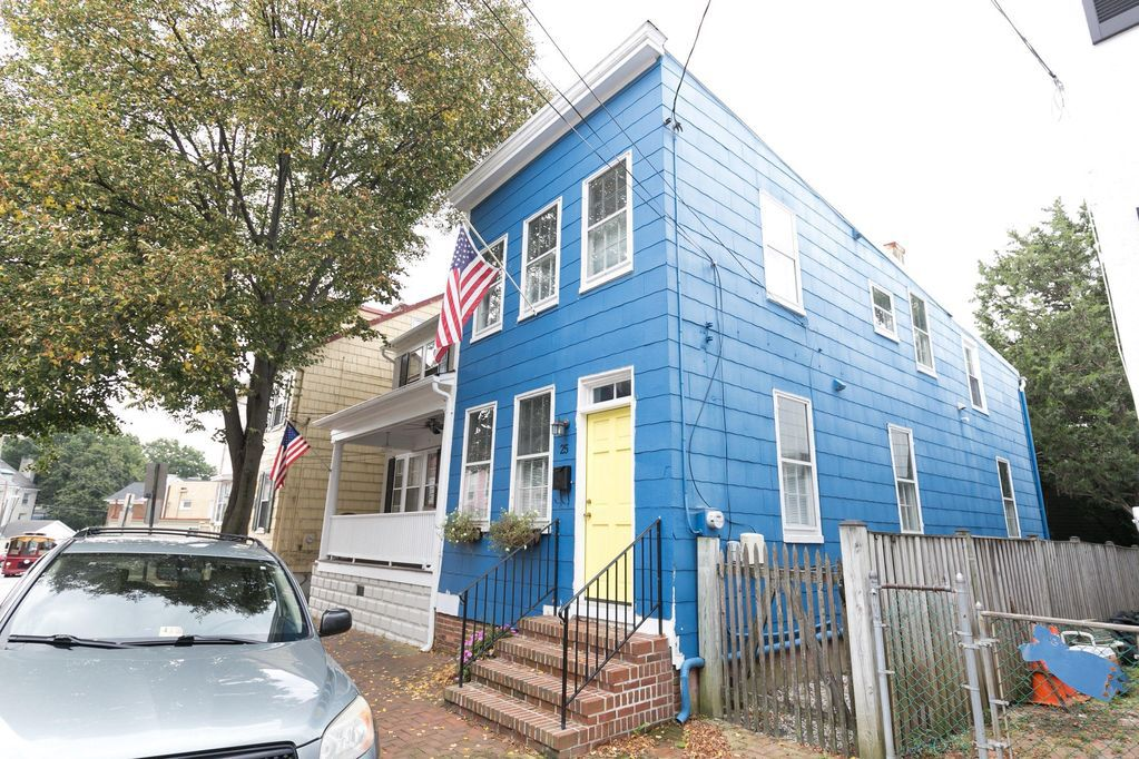 A two-story blue townhouse in Annapolis, Maryland, with an American flag outside.