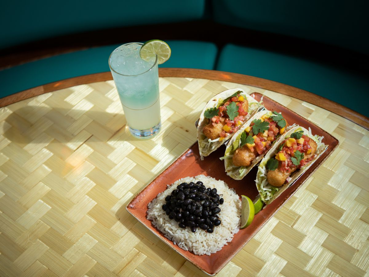 A blue drink sits on a table with three fish tacos with rice and beans.