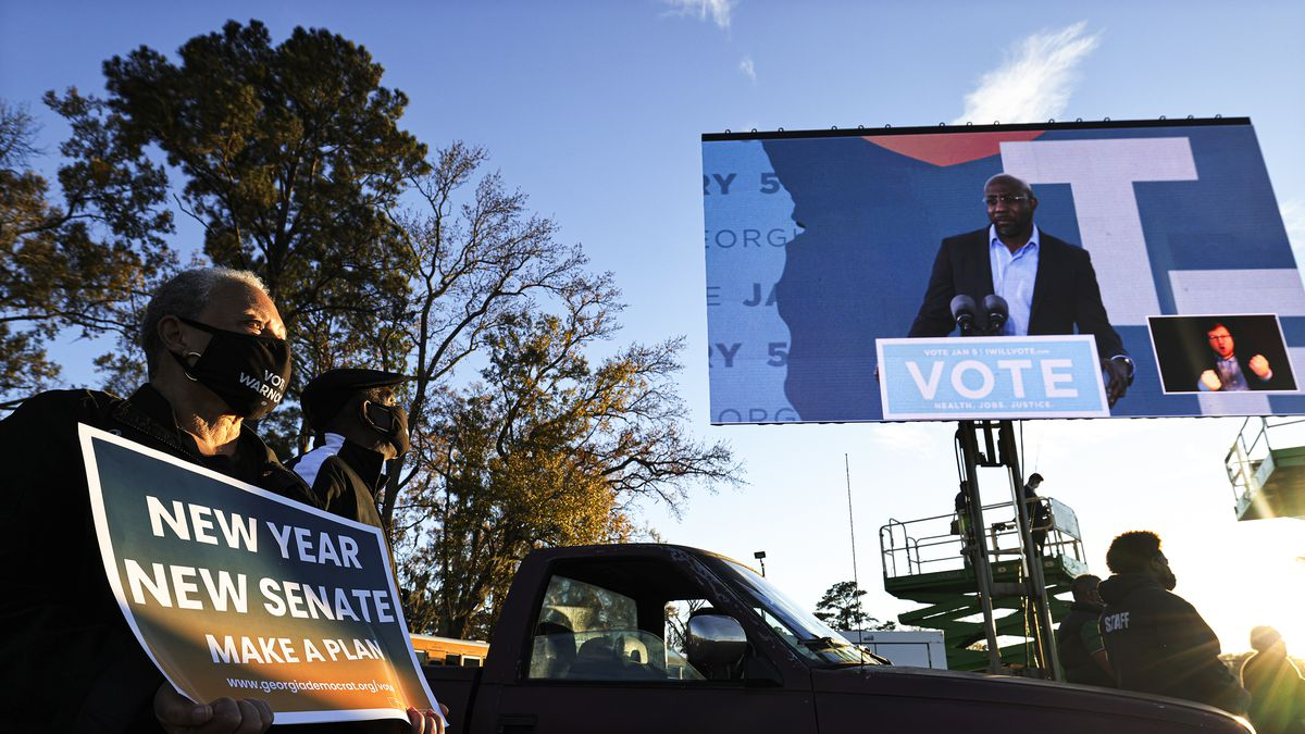"""Warnock appears in a suit without a tie on a giant flatscreen that towers above a row of cars. In the foreground, presumably perched on the roof of a car, is a masked Black man with grey hair holding a blue sign that says in white letters, """"New Year New Senate Make A Plan."""""""