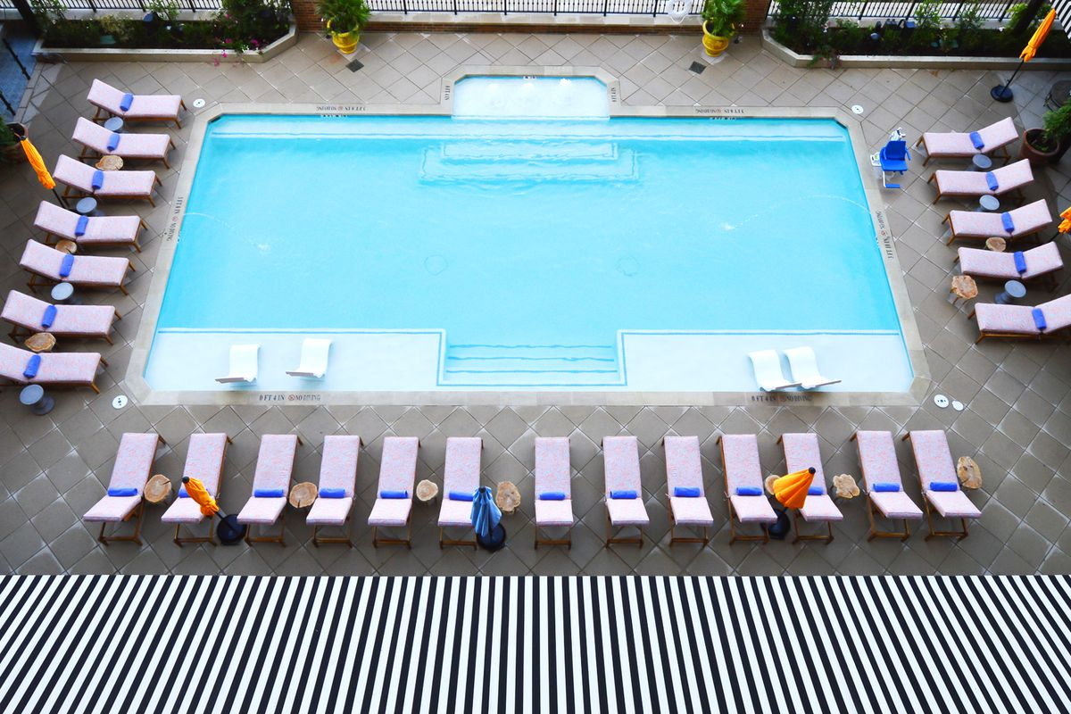 Blue pool with pink chairs and black and white awning