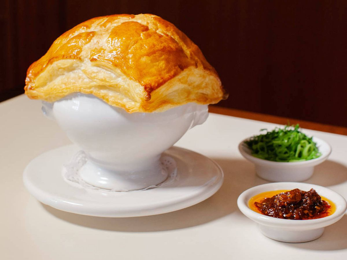 A ham hock pie, filling encased by golden pastry, in a large white pie dish, with a chilli oil dip and spring onion garnish in small ceramic dishes, also white, to its left-hand side. The vibe is very 1970s.