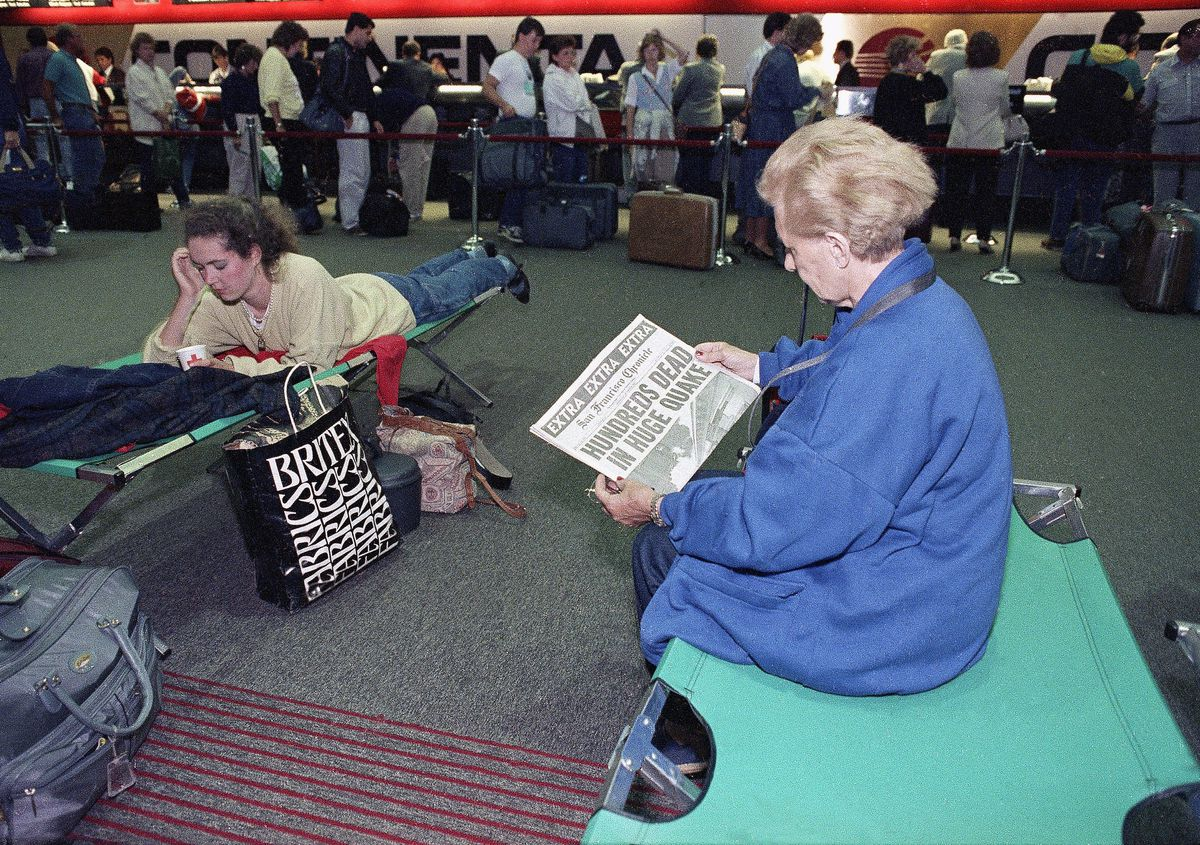 """Two women on cots, one laying down reading, the other holding a newspaper with a headline reading, """"hundreds dead in huge quake."""""""
