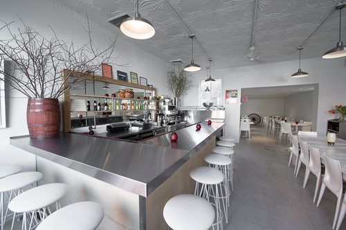 The sleek white interior of a restaurant and its metallic bar lined with white stools