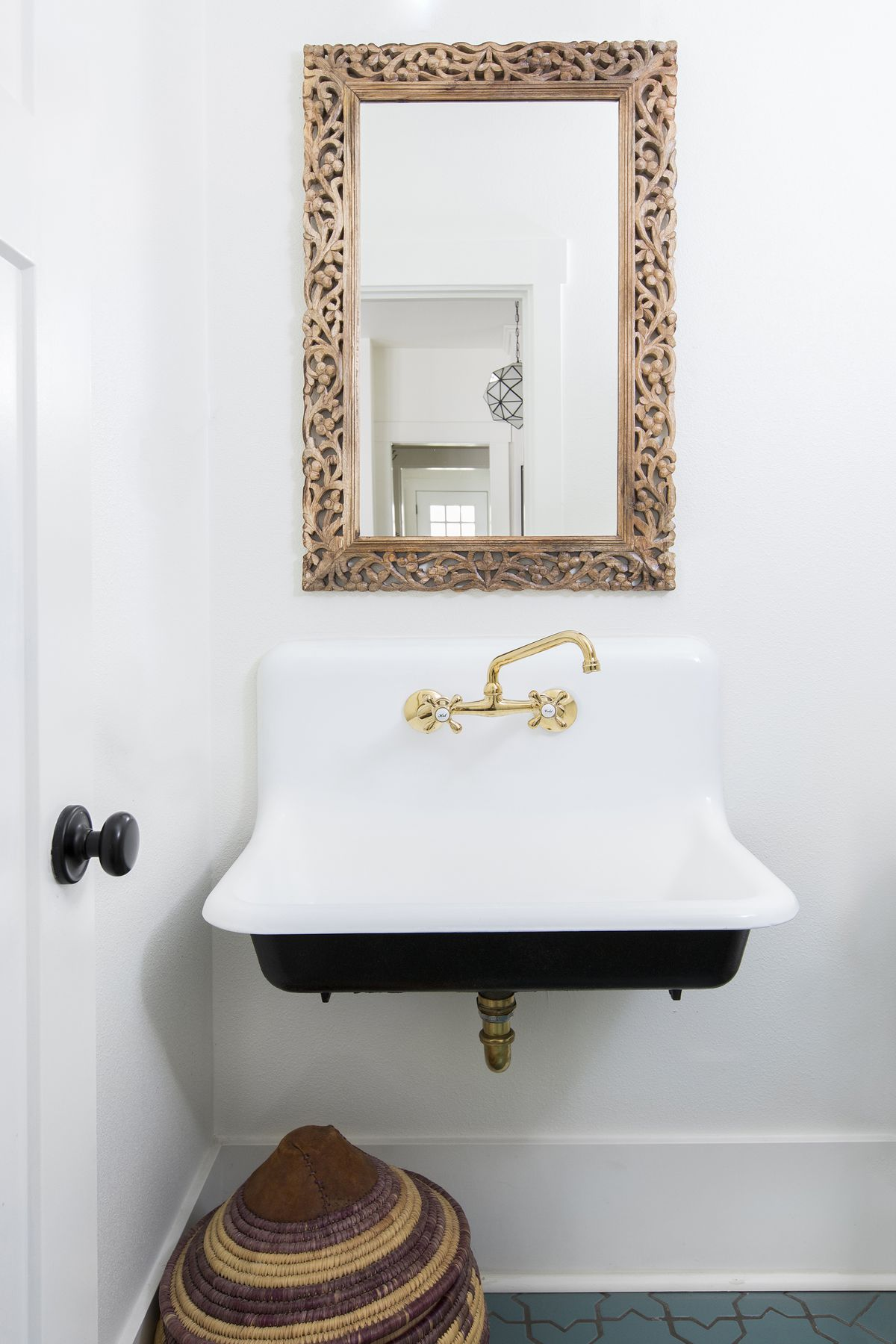 A bathroom. The sink is white. There is a mirror hanging over the sink which has an ornamental wooden frame. The walls are white.