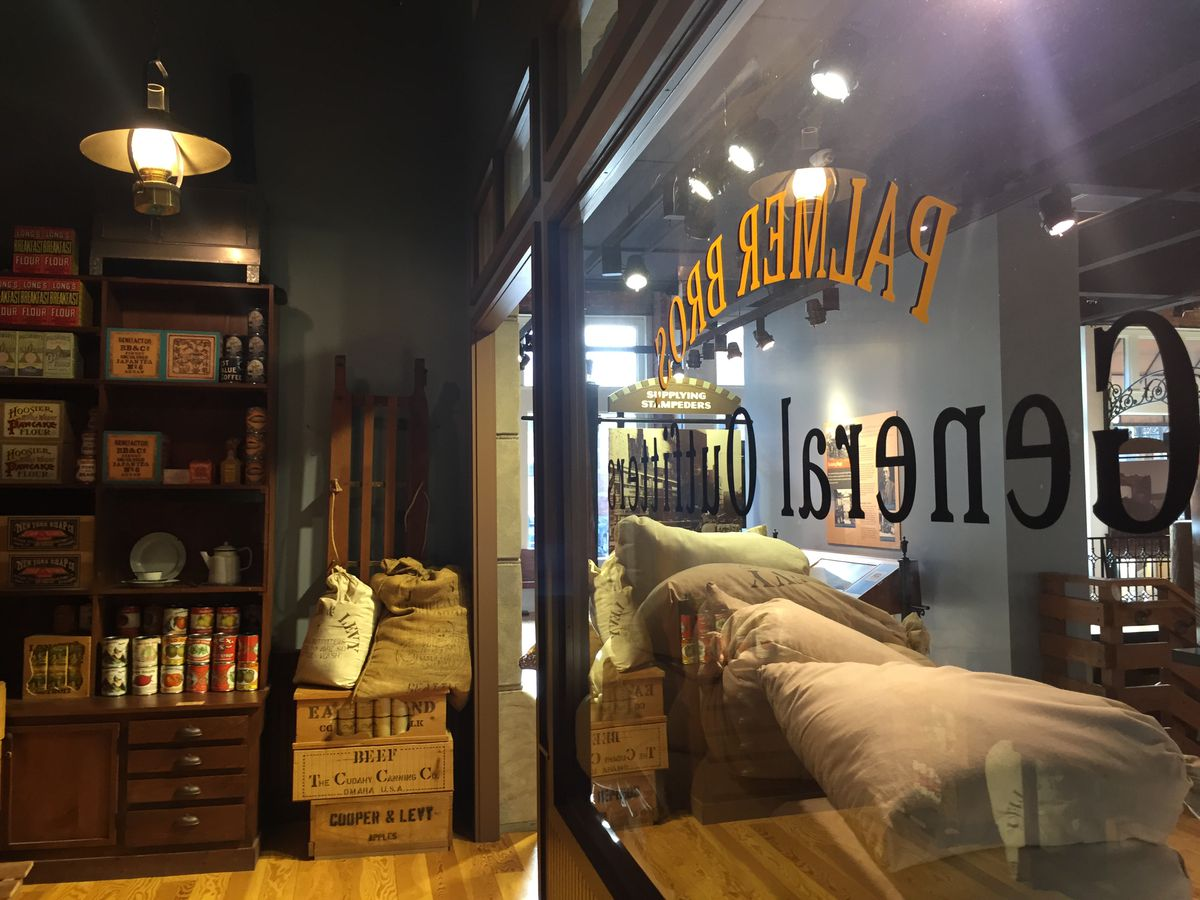 The interior of an exhibit at the Klondike Gold Rush National Historic Park. There are shelves with various objects. There is a sign on the window and multiple storage bags stacked.