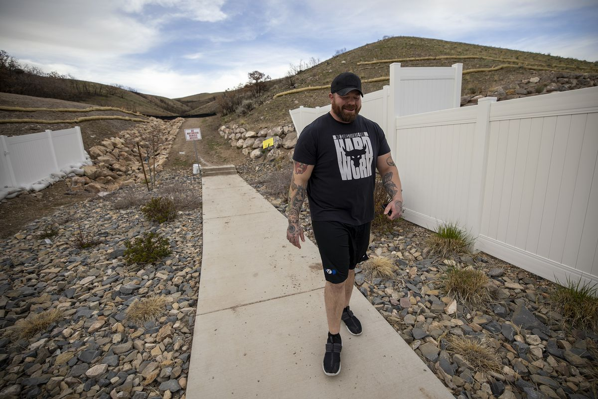 Lehi home owner Matt Gonzalez walks away from the burned area as he describes watching the 2020 Traverse Mountain Wildfire burn the hillside near his home and neighborhood in Lehi on Wednesday, April 7, 2021.