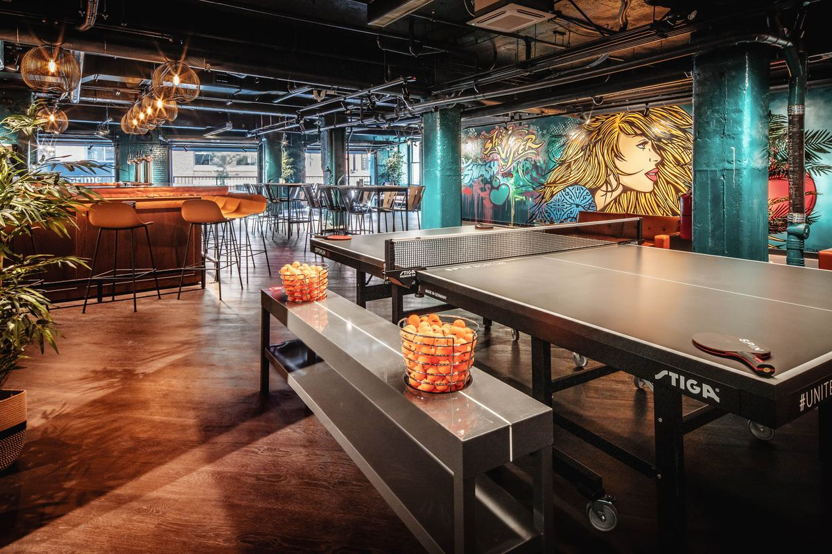 Interior shot of an empty venue with a ping-pong table, bar, and colorful mural that features a woman with long blonde hair and sunglasses.
