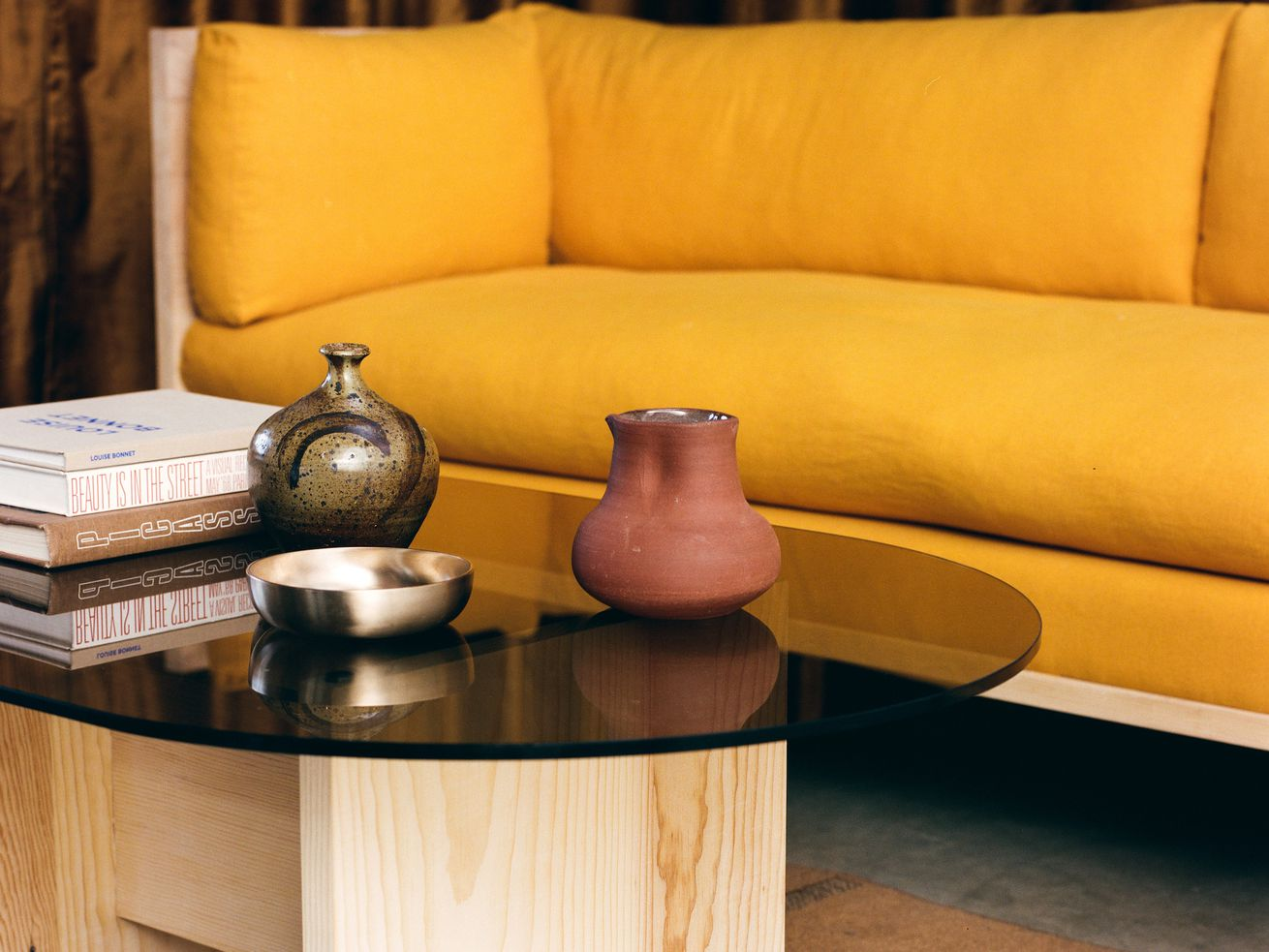 A yellow sofa, oval smoked glass coffee table with wood base, and terra cotta vessel.