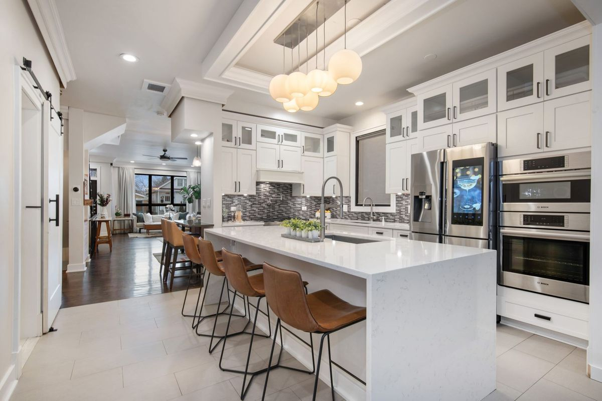 A kitchen with lots of white cabinet storage, a large waterfall edge island, and stainless steel appliances.