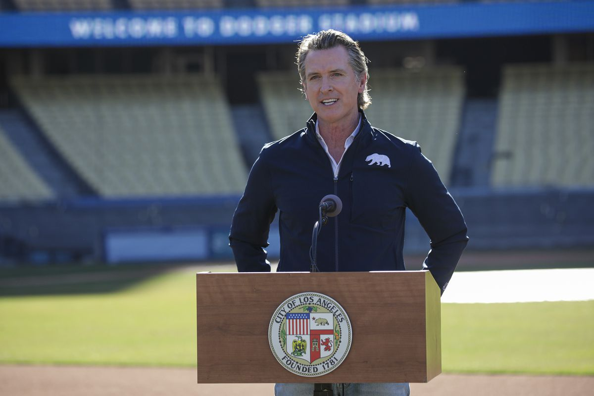 Gavin Newsom stands at a podium in Dodger Stadium.