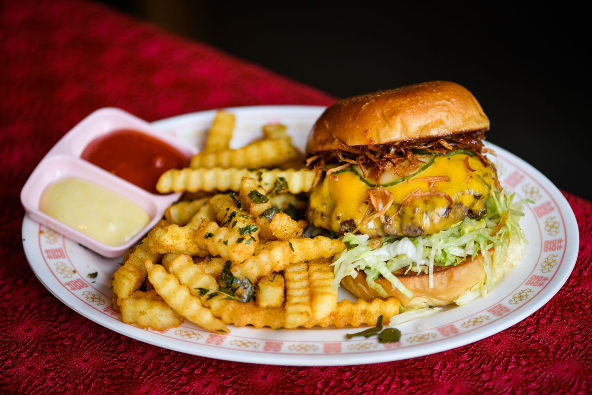 A cheeseburger topped with some sort of chili slaw and sitting on top of shredded lettuce sits on a plate next to crinkle-cut fries and a pink tray of mustard and mayo.