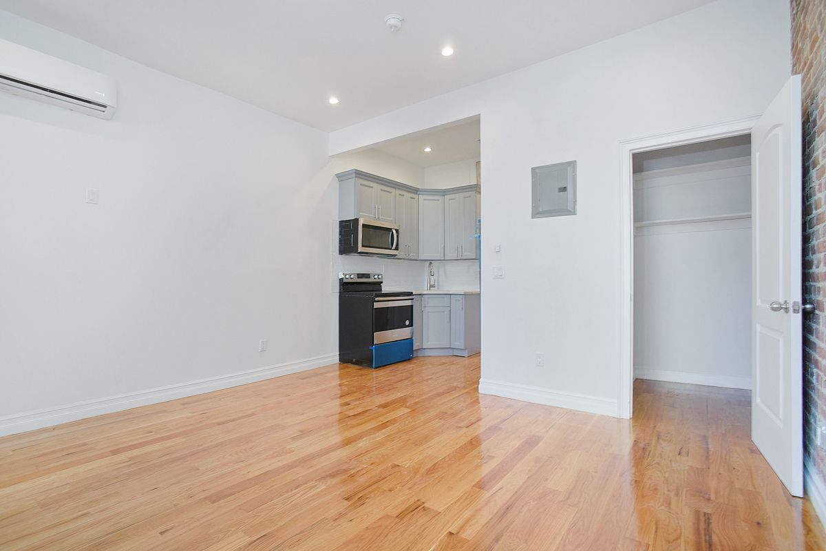 A living area with hardwood floors, white walls, and a small kitchen in the back.