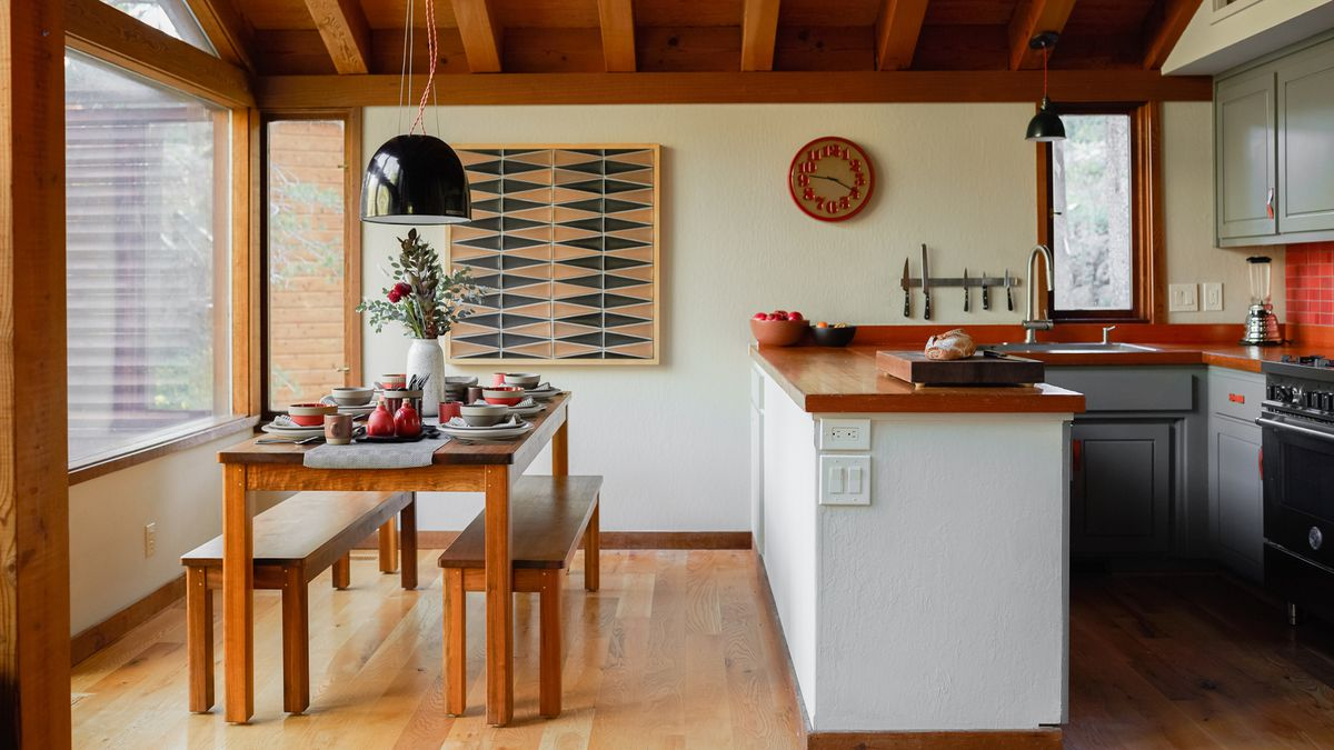A small kitchen next to an open dining area with a big wooden dining table all set for dinner.