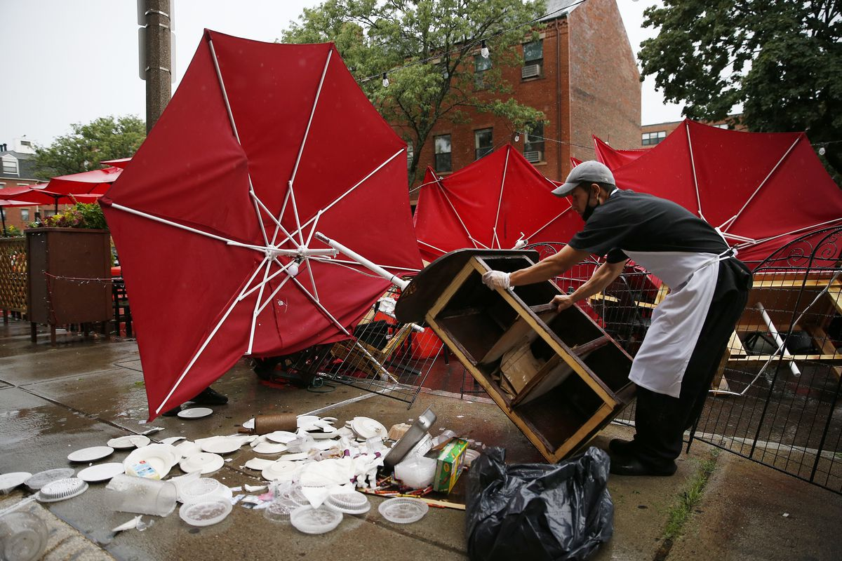 A restaurant worker cleans up an outdoor dining area that has been ruined by a thunderstorm, with large umbrellas turned inside out and plates and cutlery spilled out along the ground.