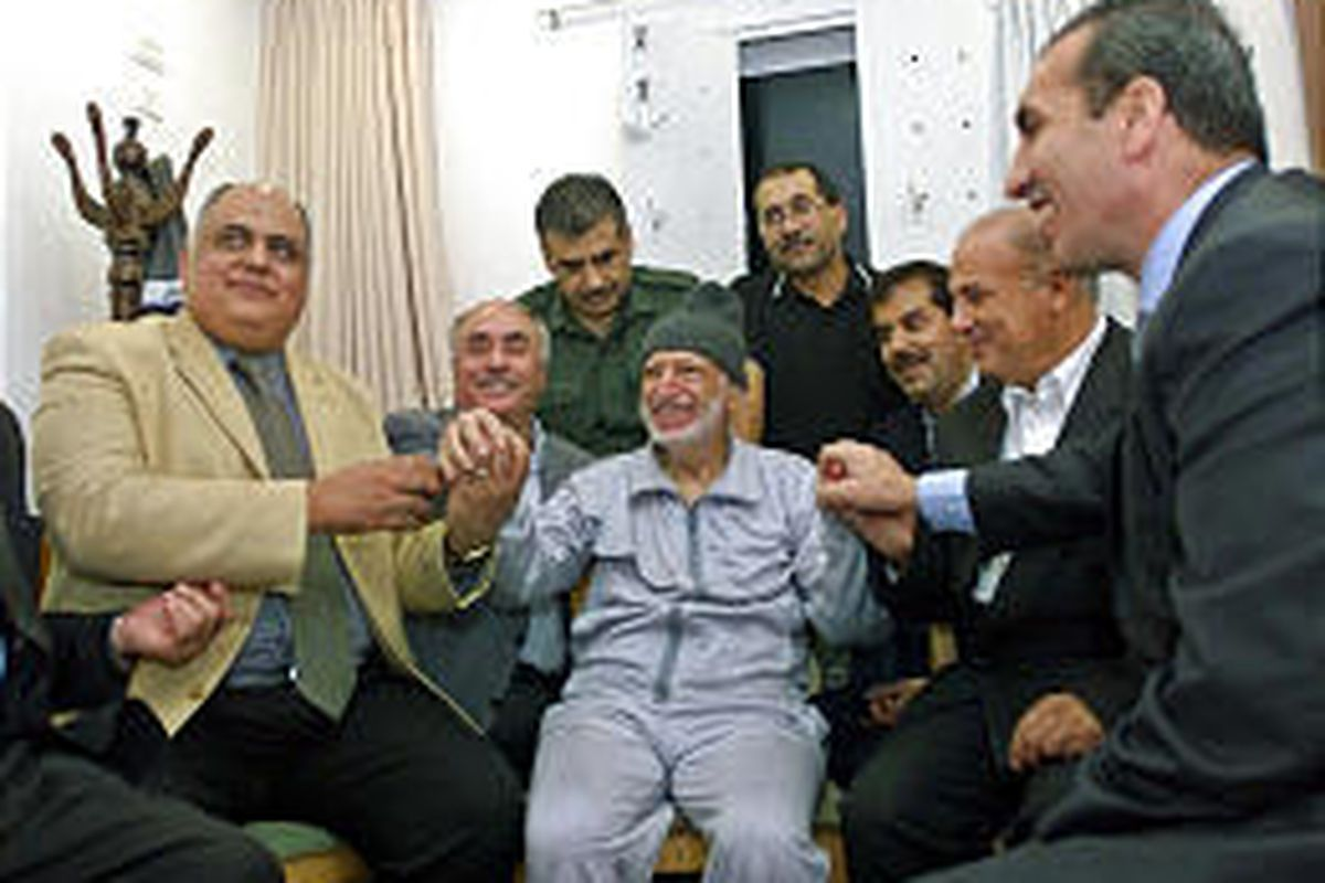 Palestinian leader Yasser Arafat, center, holds hands with his doctors at his compound in Ramallah, West Bank, Thursday afternoon.