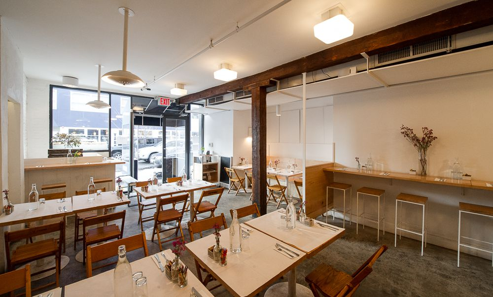 Egg's dining room, which has white tables and bar stools on the side