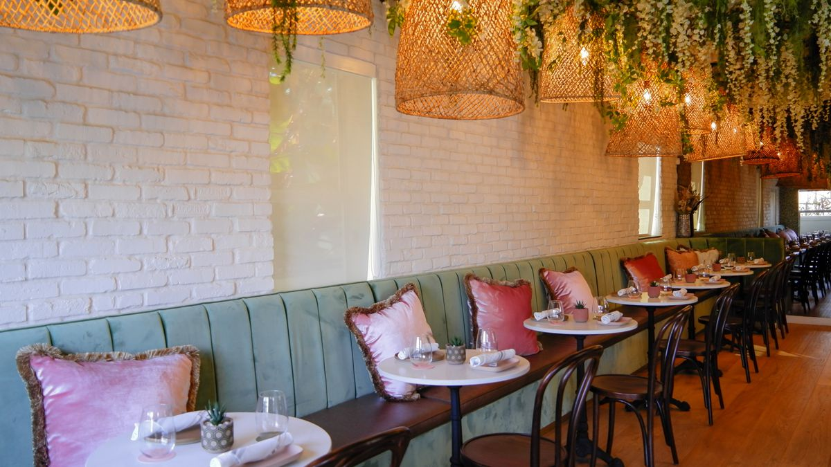 banquettes of green with pink pillows and hanging lamps