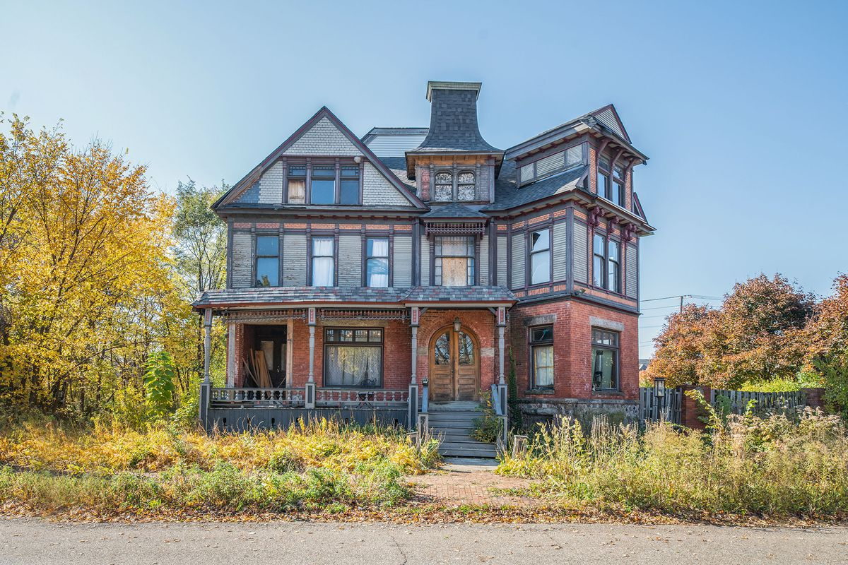A huge home with three floors and a varied facade of wood and brick. There's a few boarded up windows and missing roof shingles.