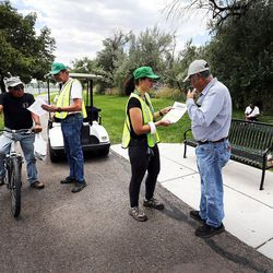 Charlie Eckhardt, second from left, and Susan Collier, second from right, of Salt Lake City Community Emergency Response Teams, hand out fliers in Salt Lake City on Monday, July 18, 2016, warning of possible toxic algae contamination in the Jordan River.