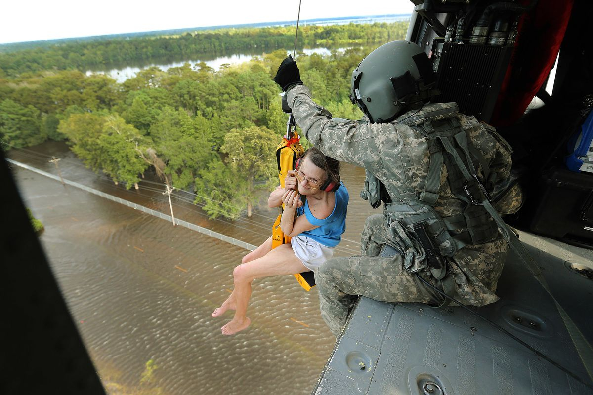 Utah Army National Guard Spc. Curtis Jeffs helps stranded flood victim Hersey Kirk after Tropical Storm Harvey in Rose City, Texas, on Thursday, Aug. 31, 2017.