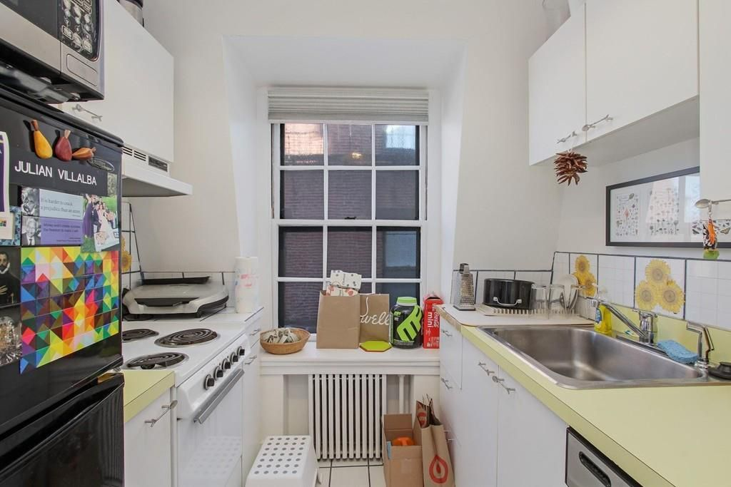 A small kitchen with counters on either side of an aisle leading to a window.