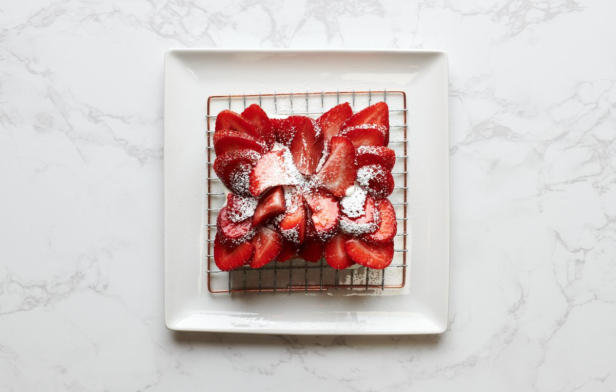 A piece of toast at Kimura Toast Bar comes layered with petals of thinly sliced strawberries, sprinkled with powdered sugar.