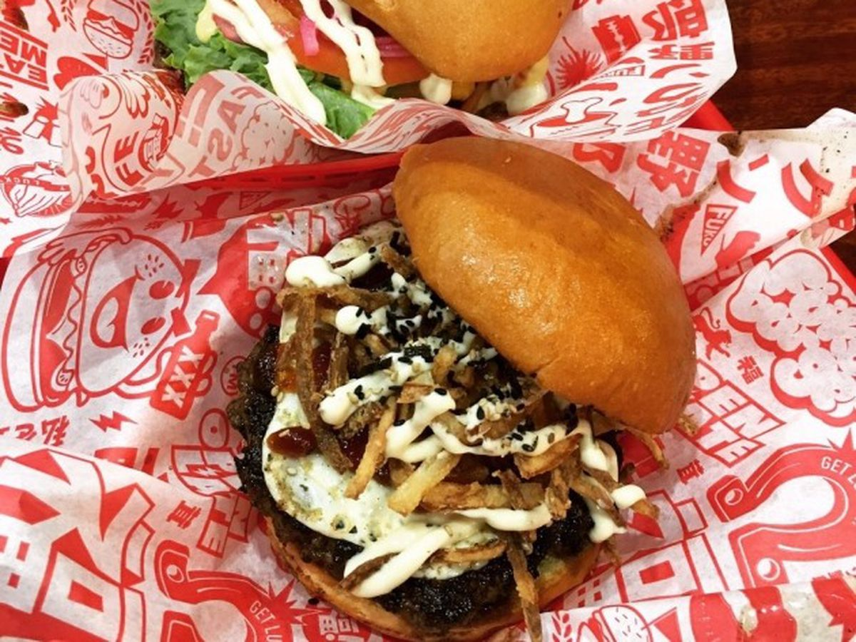 Two burgers on red and white paper