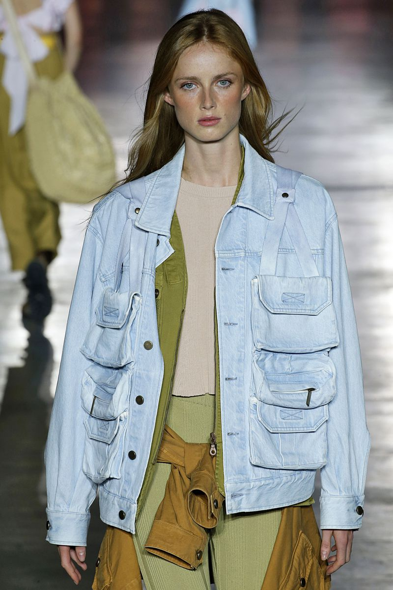 A model wears a blue denim jacket with three pockets on each breast.