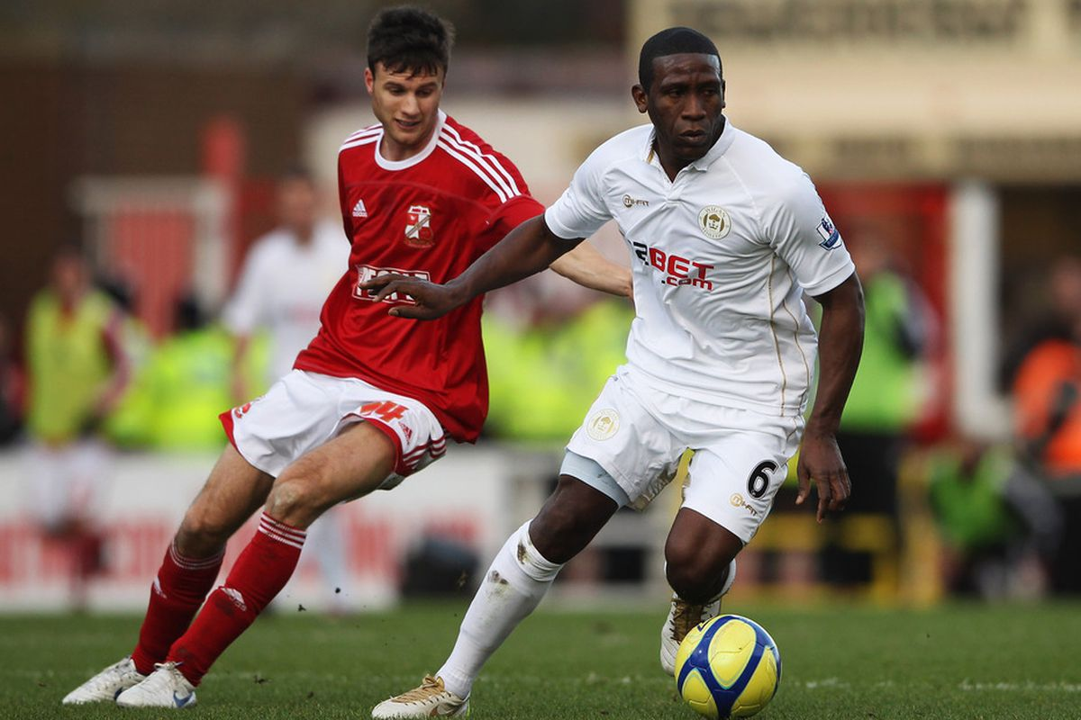 Hendry Thomas of Wigan Athletic (R) evades Jonathan Smith of Swindon Town during the FA Cup sponsored by Budweiser Third Round match between Swindon Town and Wigan Athletic at the County Ground