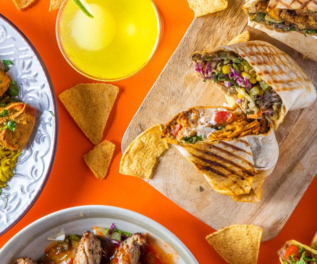 A burrito filled with meat, corn, cabbage, tomatoes, and other ingredients, sliced to reveal the inside and stacked upright on a plate next to a few other dishes out of frame and a margarita
