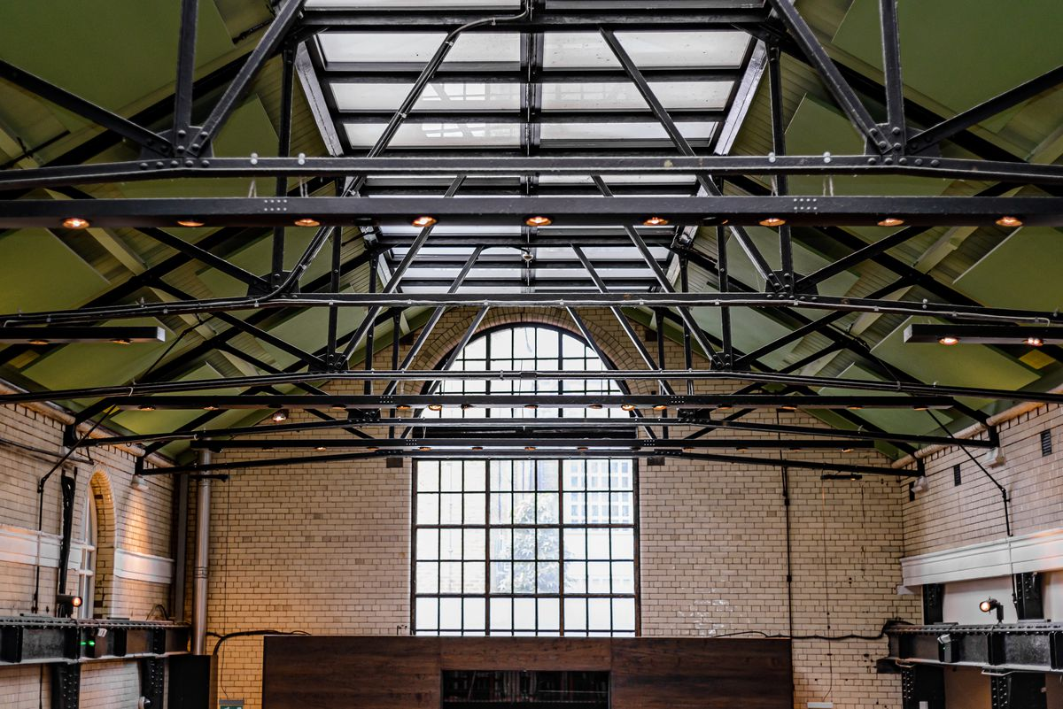 The high vaulted glass ceiling supported by black triangular beams, with an arched full-length window to the back