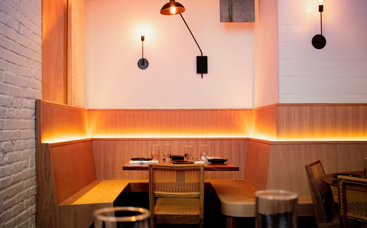 A back-lit wooden banquette runs along one side of the restaurant's dining room.