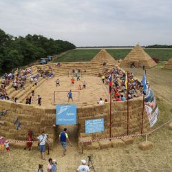 """In this photo taken on Saturday, July 22, 2017, shows a view of the arena, made of 4,500 straw bales, comes complete with tiered seating and flagpoles in Krasnoye, Stavropol region, South Russia. In a project straight out of the """"Three Little Pigs"""" fairytale, Roman Ponomarev has built a straw replica of the 643-billion-ruble ($700 million) stadium in St. Petersburg which will host World Cup semifinals. (AP Photo/Oleksandr Stashevskyi) ORG XMIT: XAZ124"""
