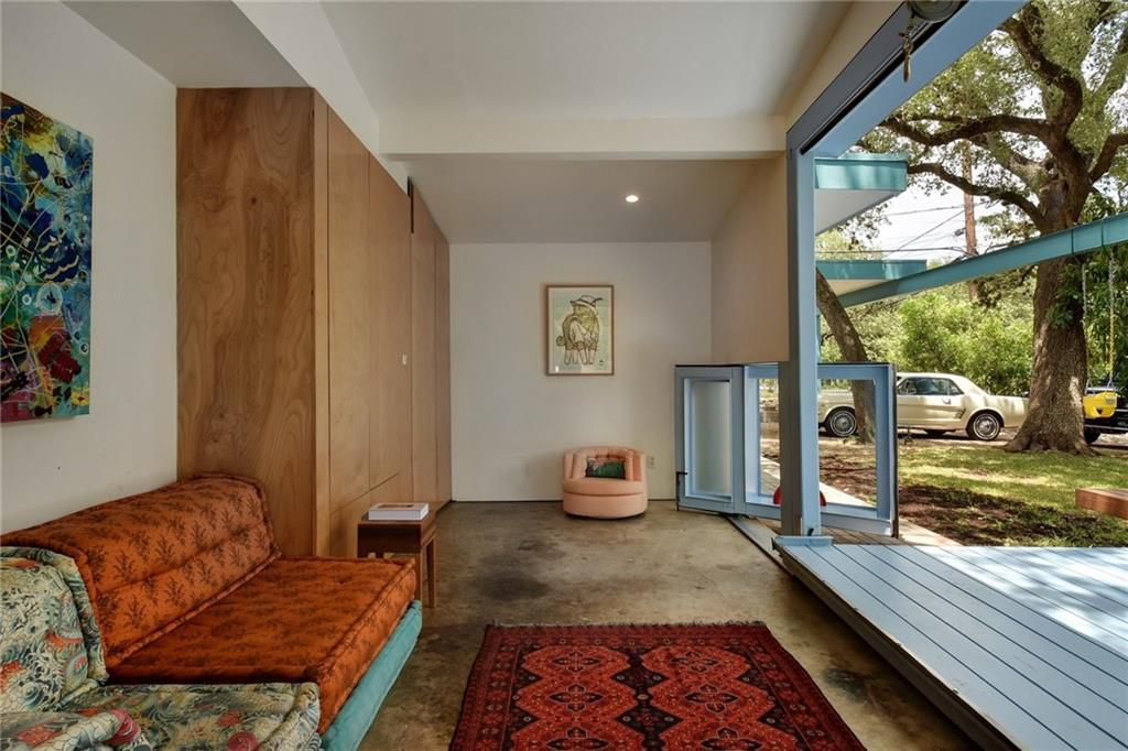 Photo of a long room with a couch against the left wall and a small rug in front of it, wall-sized wood cabinets at one end next to a small armchair. The front wall of the room is open to an outdoor deck. There is a window on a pivot on the floor on the right side wall in back. It is situated at an angle to the back wall.