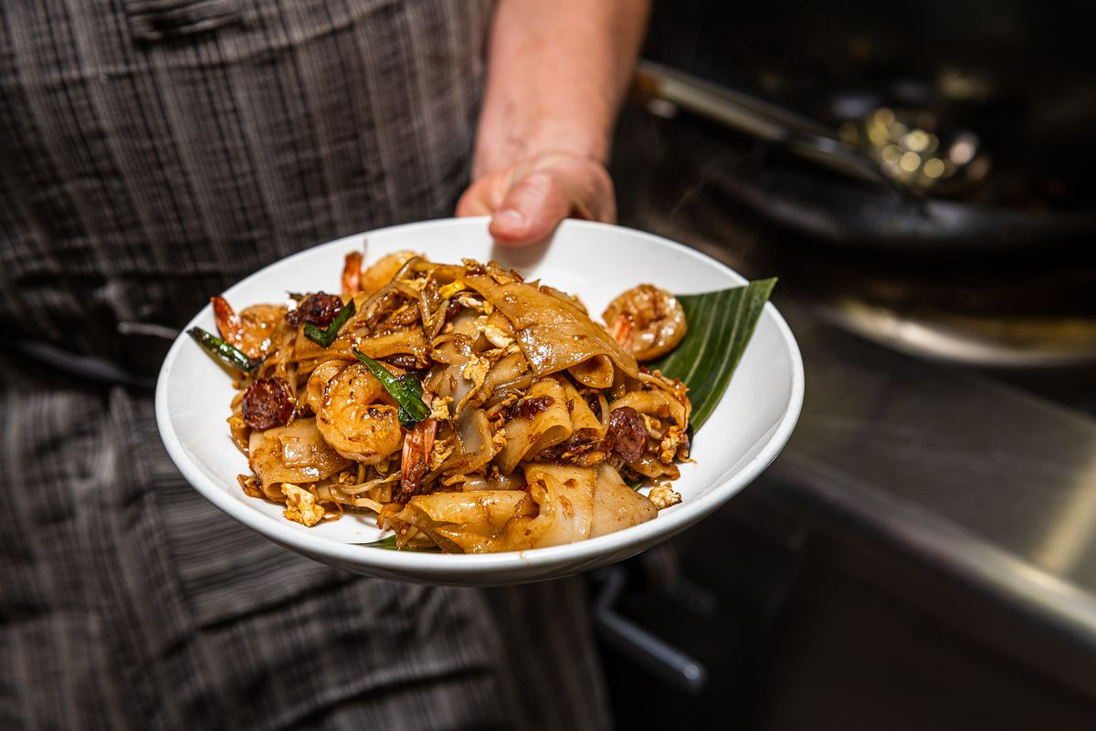 A plate of char kway teow noodles in the hands of the chef.