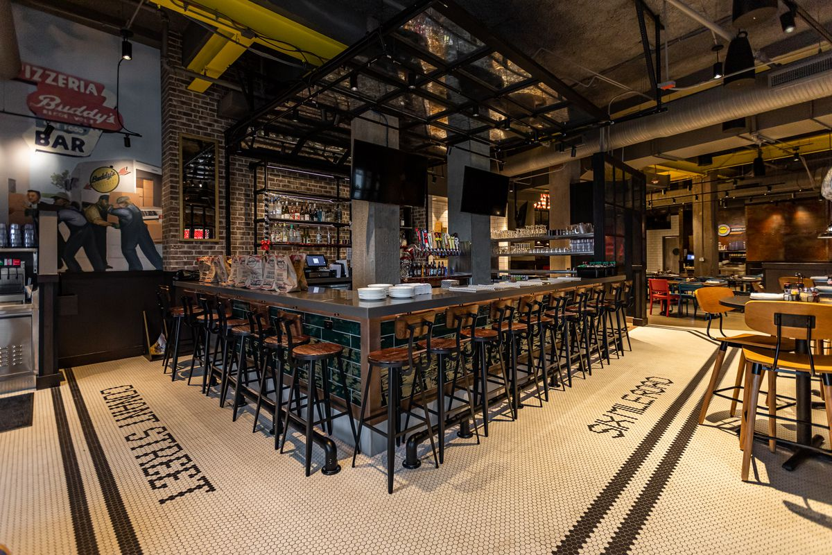 """A square bar at Buddy's is surrounded by metal and wood stools with black and white tiled floors reading """"Conant Street"""" and """"Six Mile Road."""" There are two flat-screen TVs."""