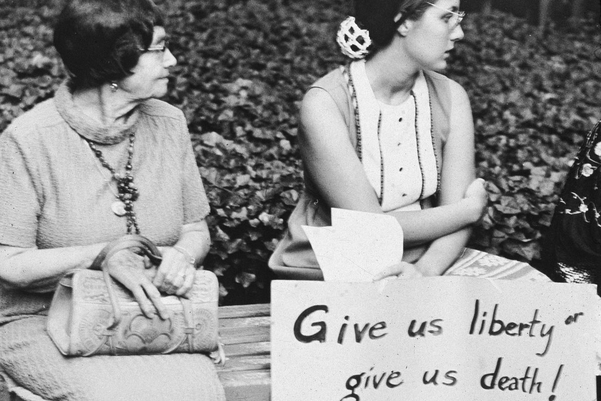 """Young woman holding a sign that reads """"Give us liberty or give us death! Pass the 26th Amendment!"""" while sitting next to a middle-aged woman on a bench at an equal rights demonstration, 1970s."""