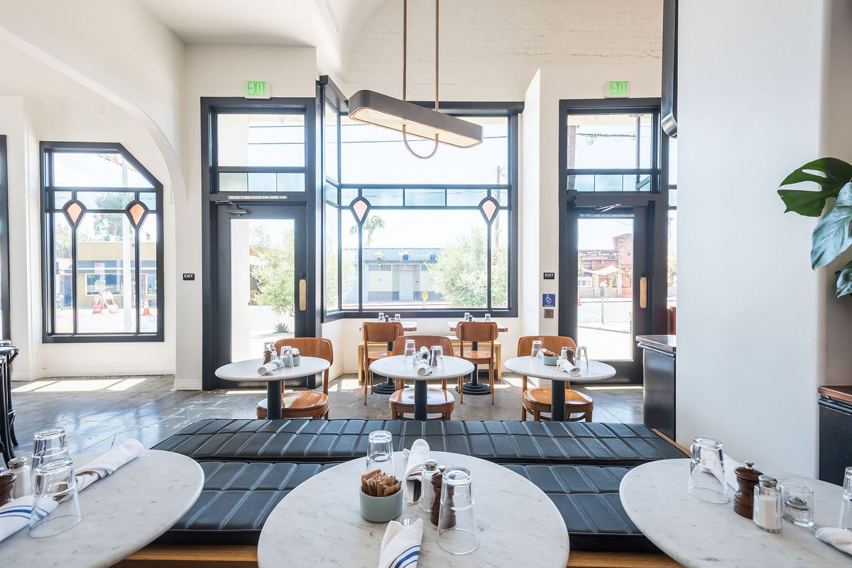 Small round tables and Art Deco glass show sunlight in a new restaurant space.
