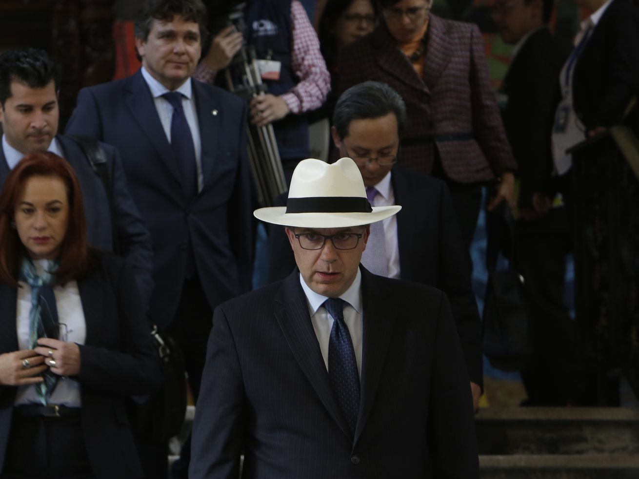 Chapman, in glasses, wearing a dark suit, blue tie, and white Panama hat, descends a flight of stairs, a crowd of diplomats and officials behind him.