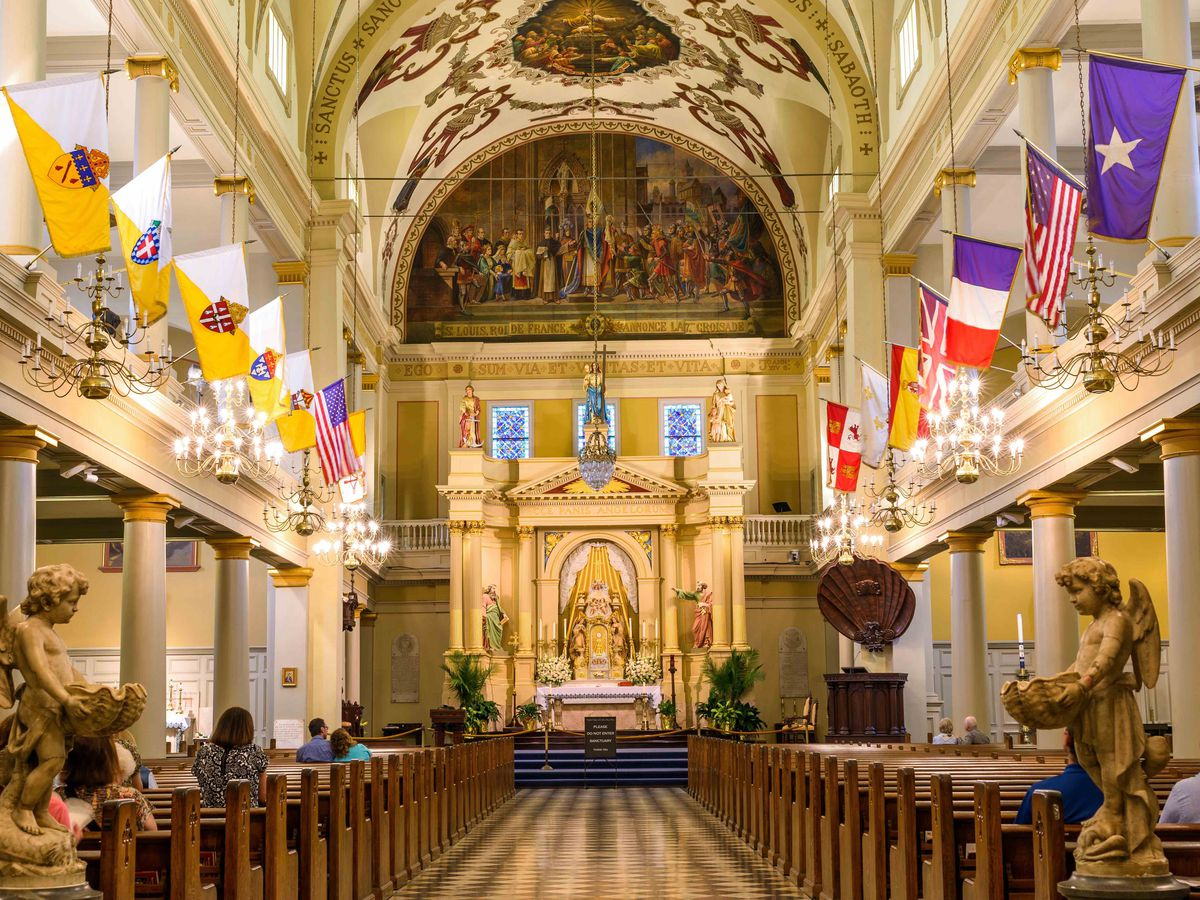 The interior of St. Louis Cathedral in New Orleans. The ceiling is high and arched. There are various flags lining the walls above the pews.