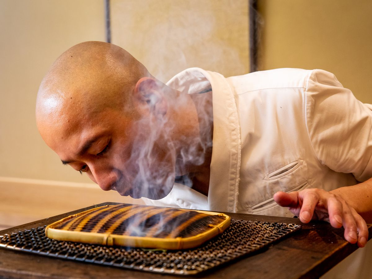 Noz chef Nozomu Abe blows over a portable grill he's using to lightly smoke sea eel