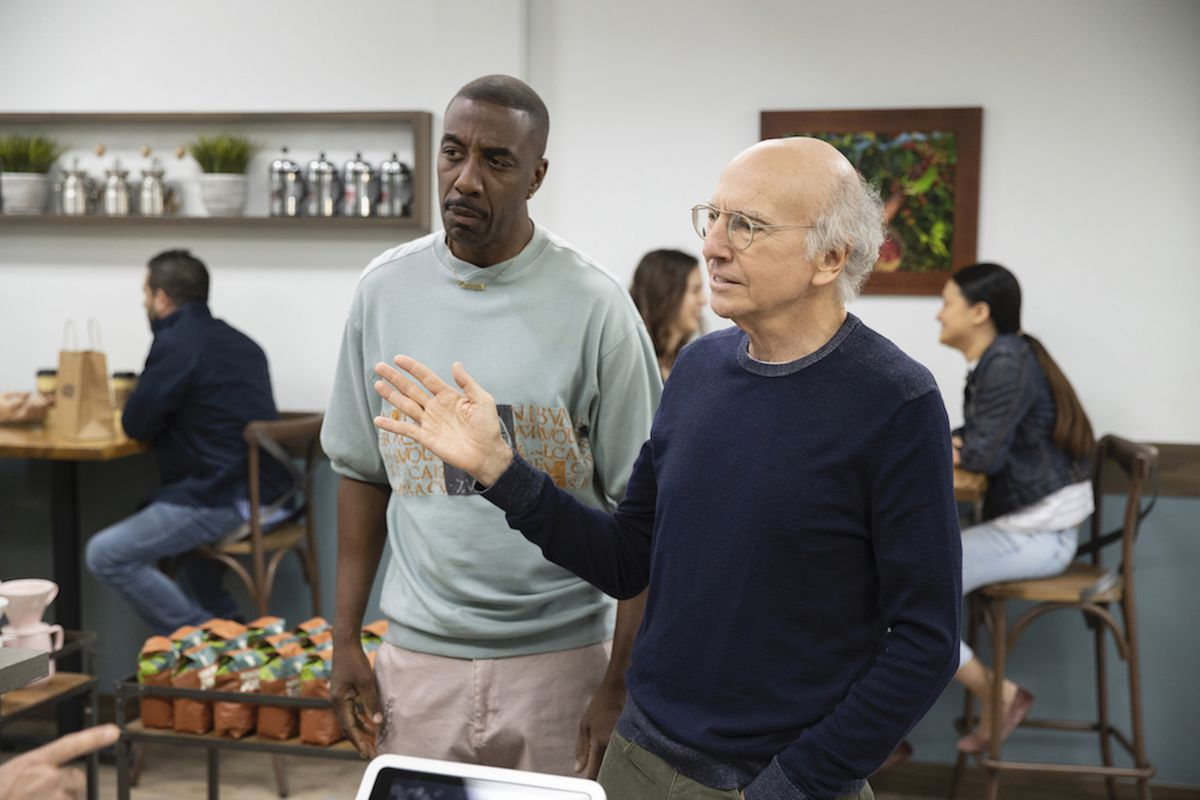 In a coffee shop, JB Smoove, wearing a light blue t-shirt and khakis, stands next to Larry David in a navy sweater.