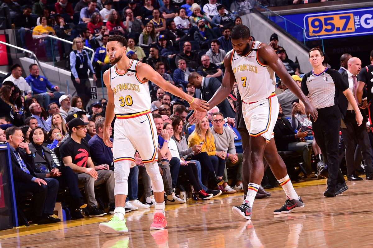 Stephen Curry of the Golden State Warriors high-fives Eric Paschall of the Golden State Warriors on March 5, 2020 at Chase Center in San Francisco, California.