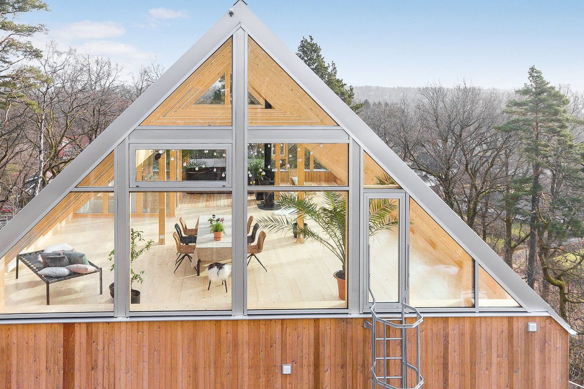 Shot of the top floor of a home with a transparent glass roof set among the woods.