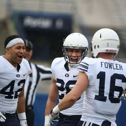 BYU's Johnny Tapusoa, left, Mitchell Price and Gavin Fowler celebrate Price's tackle during the Blue-White game at LaVell Edwards Stadium in Provo on Saturday, April 7, 2018.