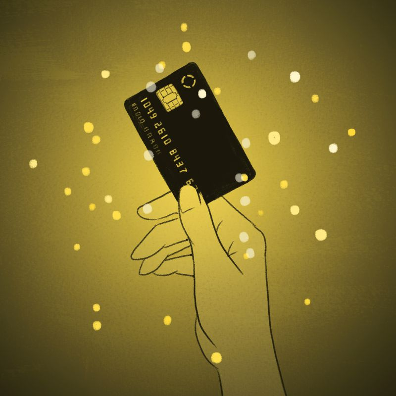 A hand holds  a credit card