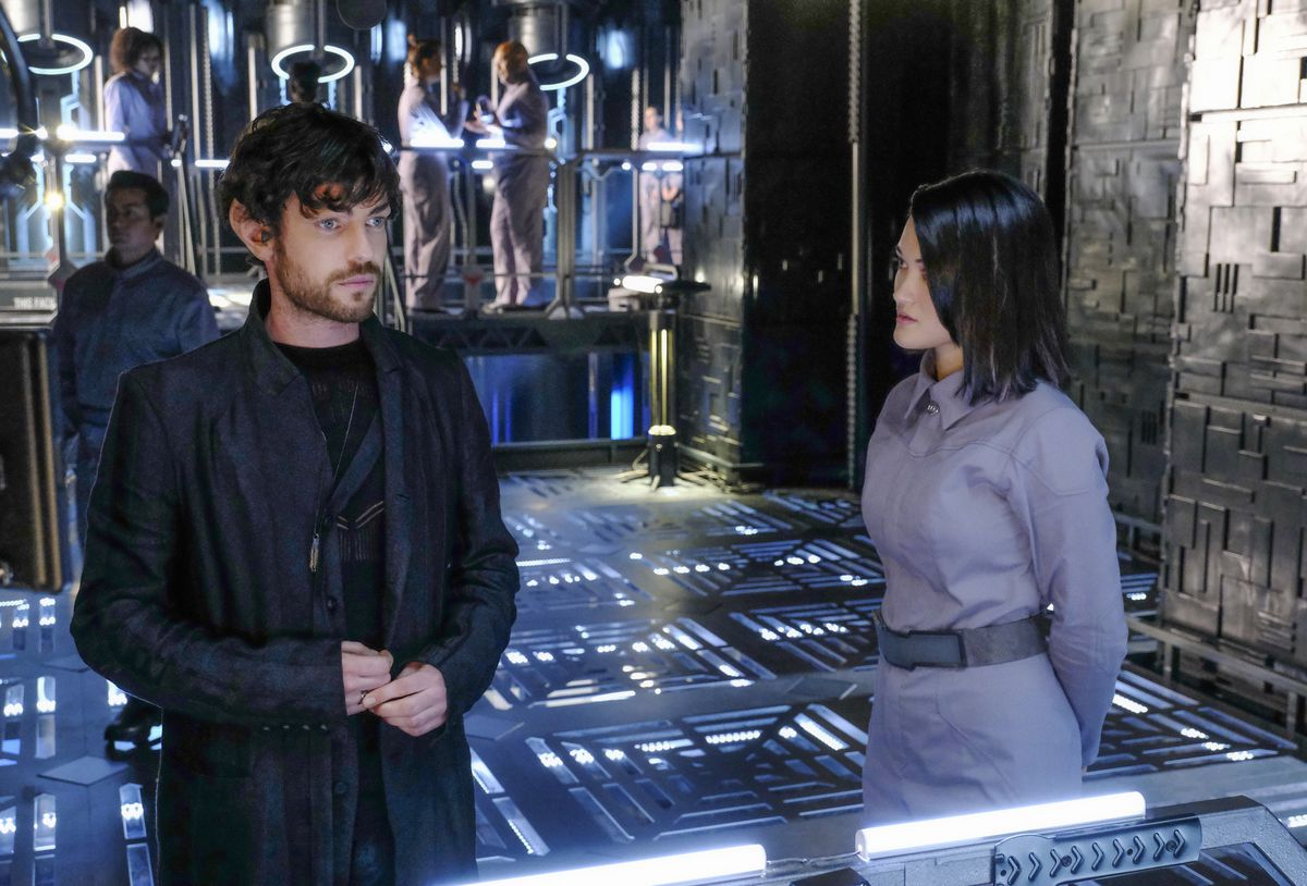 A pale, bearded young Romulan in dark blue robes stands on the deck of a Borg cube, surrounded by dark grating and bright white lights, next to a young dark-haired humanoid woman in gray.
