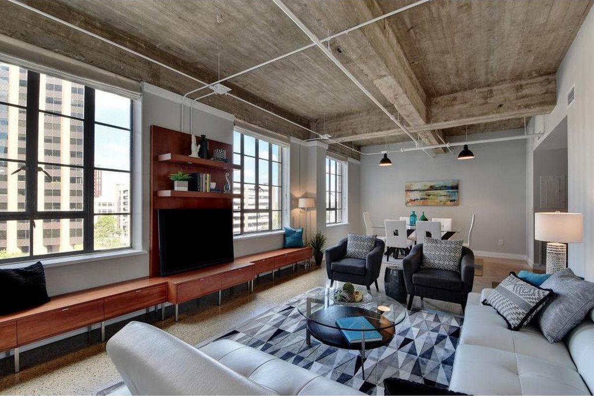 Living room of loft-like space with industrial ceiling, big windows, furnished