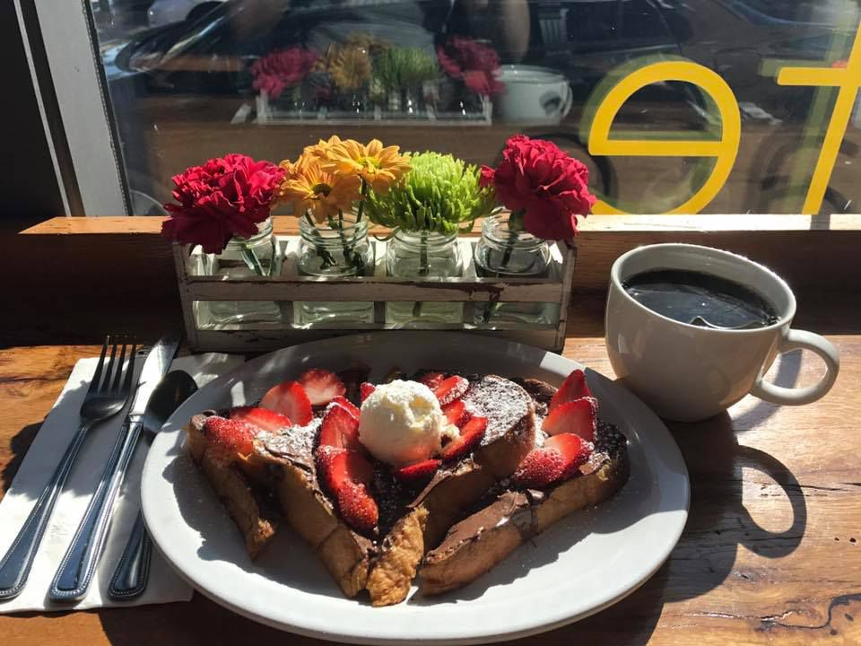 A plate of French toast sits on a restaurant counter by a sunny window